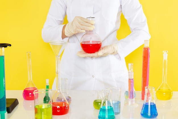Vista frontale di giovane chimico femminile in vestito bianco che tiene le soluzioni chimiche