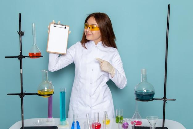 Vista frontale di giovane chimico femminile in vestito bianco davanti al blocco note del whtie della tenuta della tavola