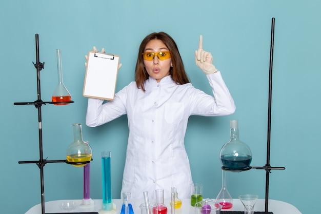 Vista frontale di giovane chimico femminile in vestito bianco davanti al blocco note della tenuta della tavola