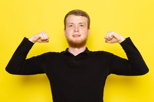 Vista frontale di giovane maschio in camicia nera che posa e che flette sulla superficie gialla