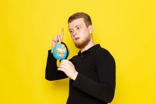Vista frontale di giovane maschio in camicia nera che tiene piccolo globo
