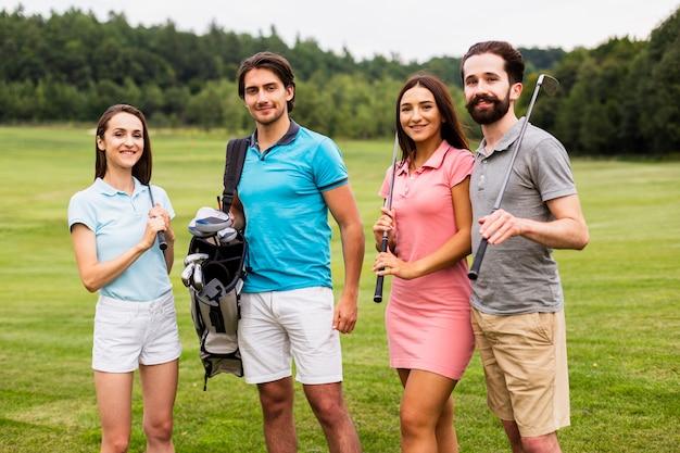 Vista frontale di giovani giocatori di golf che esaminano macchina fotografica