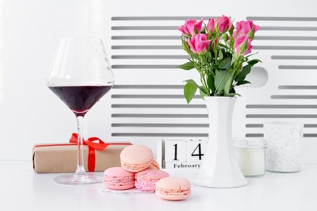 Vista frontale di macarons con bicchiere di vino e vaso di rose