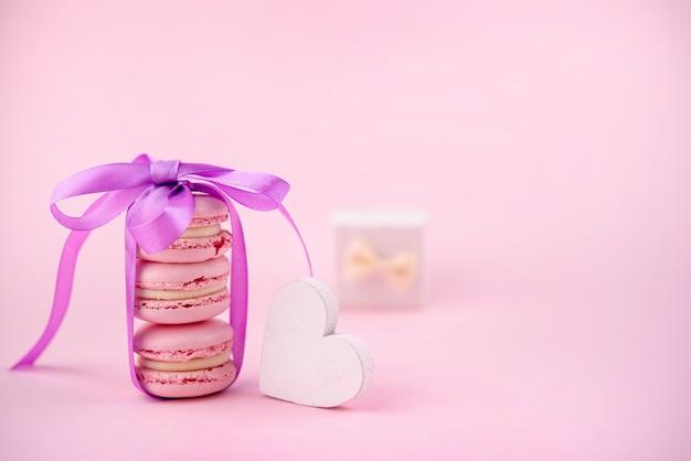 Vista frontale di macarons impilati con nastro e cuore