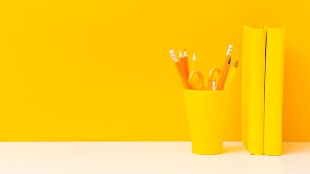 Vista frontale di matite e libri gialli