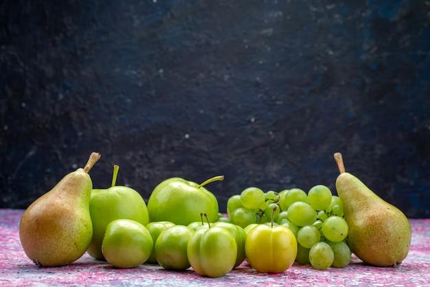 Vista frontale di mele e uva insieme a pere e prugne ciliegia sulla superficie blu scuro