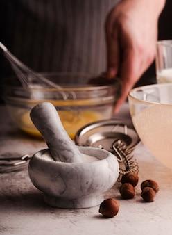 Vista frontale di mortaio e pestello con castagne e cuoco sfocato