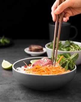 Vista frontale di noodles con carote e copia spazio