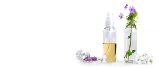 Vista frontale di olio essenziale e petali di fiori in bottiglia in formato panoramico