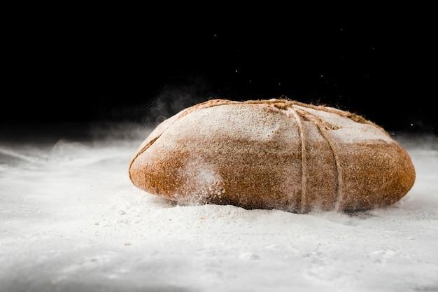 Vista frontale di pane e farina su fondo nero