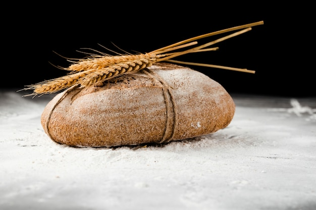 Vista frontale di pane e grano su farina