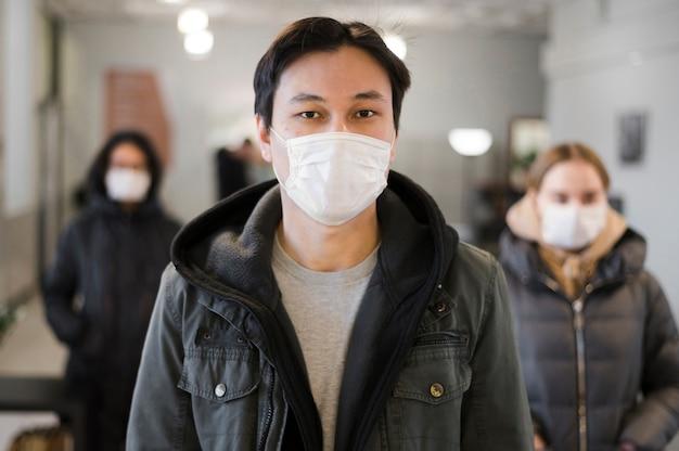 Vista frontale di persone con maschere mediche