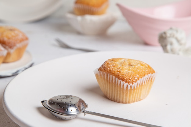 Vista frontale di piccole deliziose torte cotte al forno e squisite sulla superficie bianca