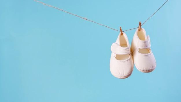 Vista frontale di piccole scarpe di bambino sveglie con lo spazio della copia