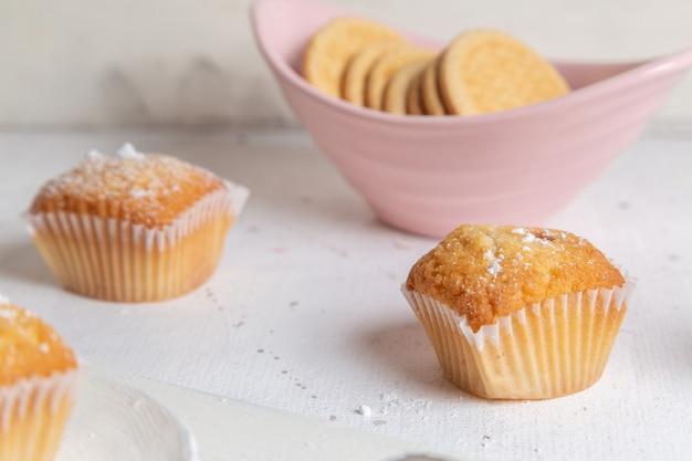 Vista frontale di piccoli dolci cotti e squisiti con i biscotti sulla superficie bianca
