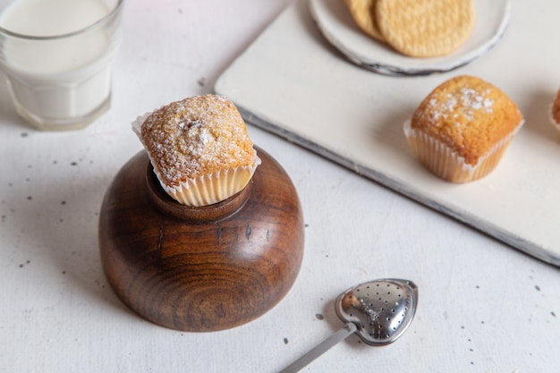 Vista frontale di piccoli dolci squisiti con zucchero in polvere e bicchiere di latte sulla superficie bianca