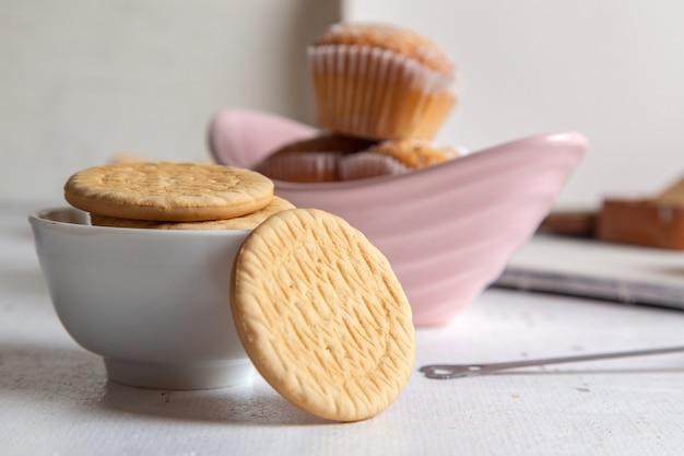 Vista frontale di piccoli dolci squisiti con zucchero in polvere e biscotti sulla superficie bianca