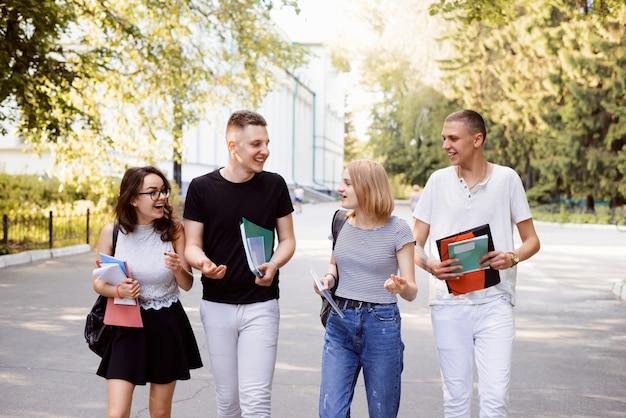 Vista frontale di quattro studenti che camminano e parlano in un campus universitario, si divertono molto dopo le lezioni con gli amici, conversano insieme