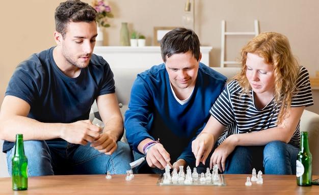 Vista frontale di tre amici che giocano a scacchi
