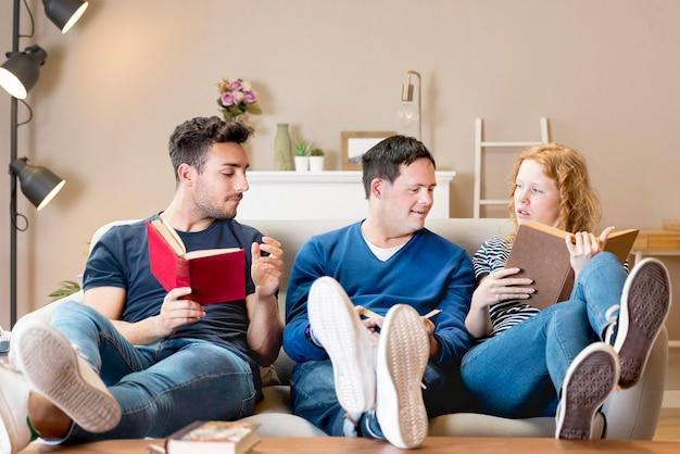 Vista frontale di tre amici sul divano con i libri