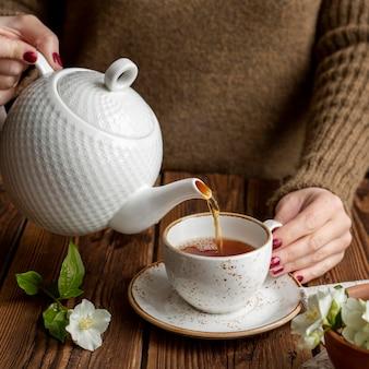 Vista frontale di un concetto di versamento del tè della persona