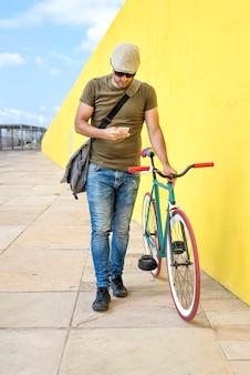 Vista frontale di un giovane uomo alla moda con una bici fissa