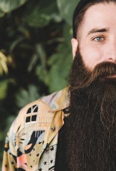 Vista frontale di un giovane uomo con la barba lunga che guarda l'obbiettivo