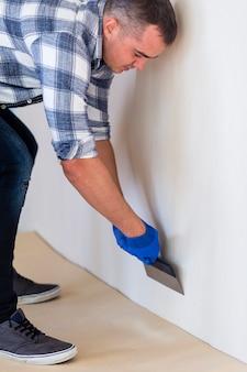 Vista frontale di un uomo che lavora su un muro