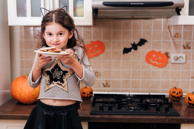 Vista frontale di una bambina con un piatto di biscotti