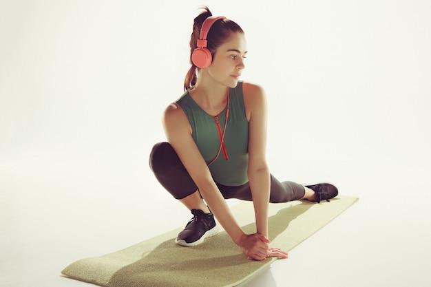Vista frontale di una giovane donna che allunga corpo nella classe di ginnastica.