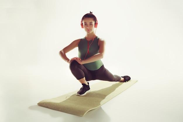 Vista frontale di una giovane donna che allunga il corpo nella classe di ginnastica.