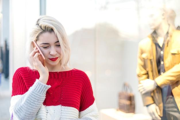 Vista frontale di una giovane donna in piedi mentre si utilizza il telefono cellulare