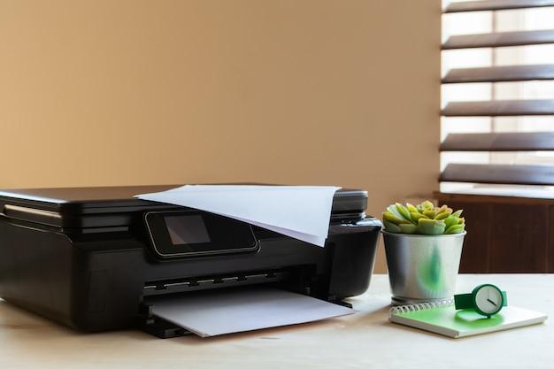 Vista frontale di una macchina stampante nera su un tavolo