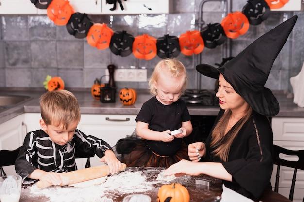 Vista frontale di una madre e dei suoi bambini che producono i biscotti di halloween