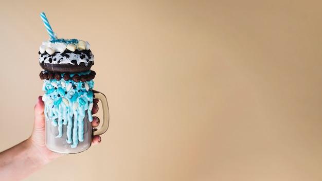 Vista frontale di una mano che tiene un frappè con sfondo chiaro