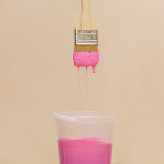 Vista frontale di vernice rosa e pennello