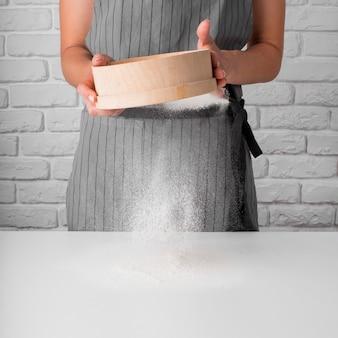 Vista frontale donna che setaccia farina