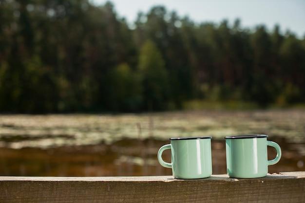 Vista frontale due tazze sul ponte di legno