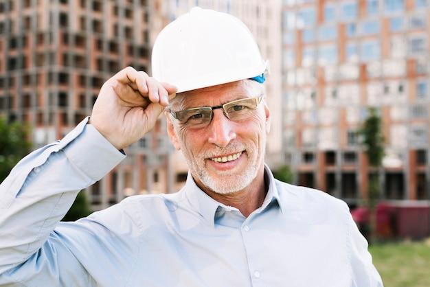 Vista frontale felice vecchio con casco bianco