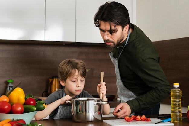 Vista frontale figlio e padre cucinare
