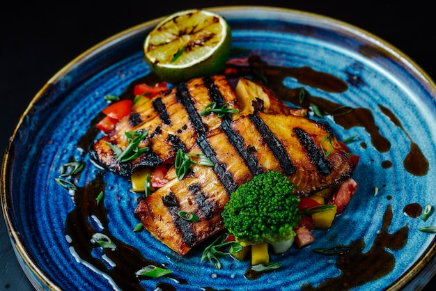 Vista frontale filetto di pesce alla griglia con verdure e una fetta di limone su un piatto