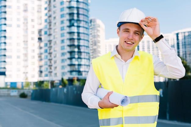 Vista frontale giovane architetto con piani e casco