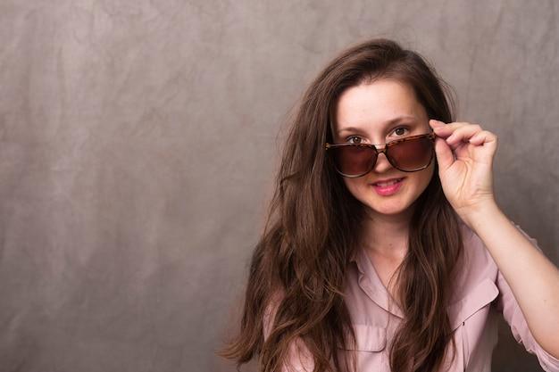 Vista frontale giovane donna con gli occhiali da sole