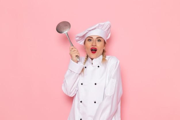 Vista frontale giovane donna cuoco in abito bianco holdingsilver cucchiaio sorridente sullo spazio rosa cuoco cucina lavoro lavoro foto
