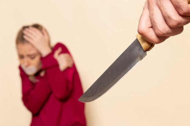 Vista frontale giovane femmina in camicia rossa con la bocca legata paura del coltello sulla foto panno crema spazio femminile