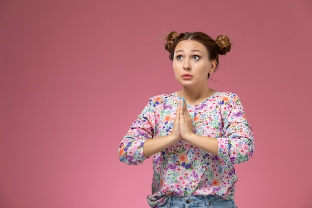 Vista frontale giovane femmina in fiore progettato camicia e blue jeans in posa nella posa di preghiera sullo sfondo rosa