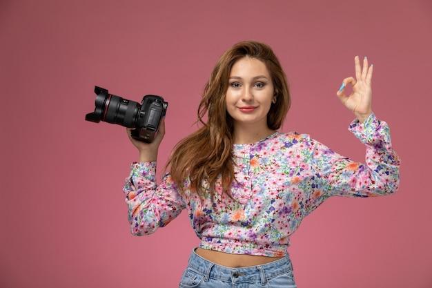 Vista frontale giovane femmina in fiore progettato camicia e blue jeans tenendo la fotocamera sorridendo leggermente su sfondo rosa