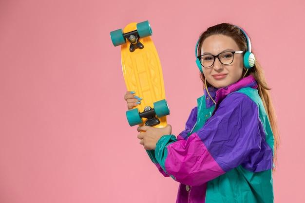 Vista frontale giovane femmina in t-shirt bianca ed cappotto ascoltando musica tramite auricolari tenendo lo skateboard sullo sfondo rosa