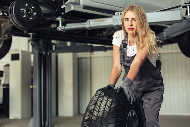 Vista frontale giovane meccanico femminile ruota spingendo