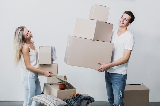 Vista frontale giovane uomo e donna con scatole in movimento